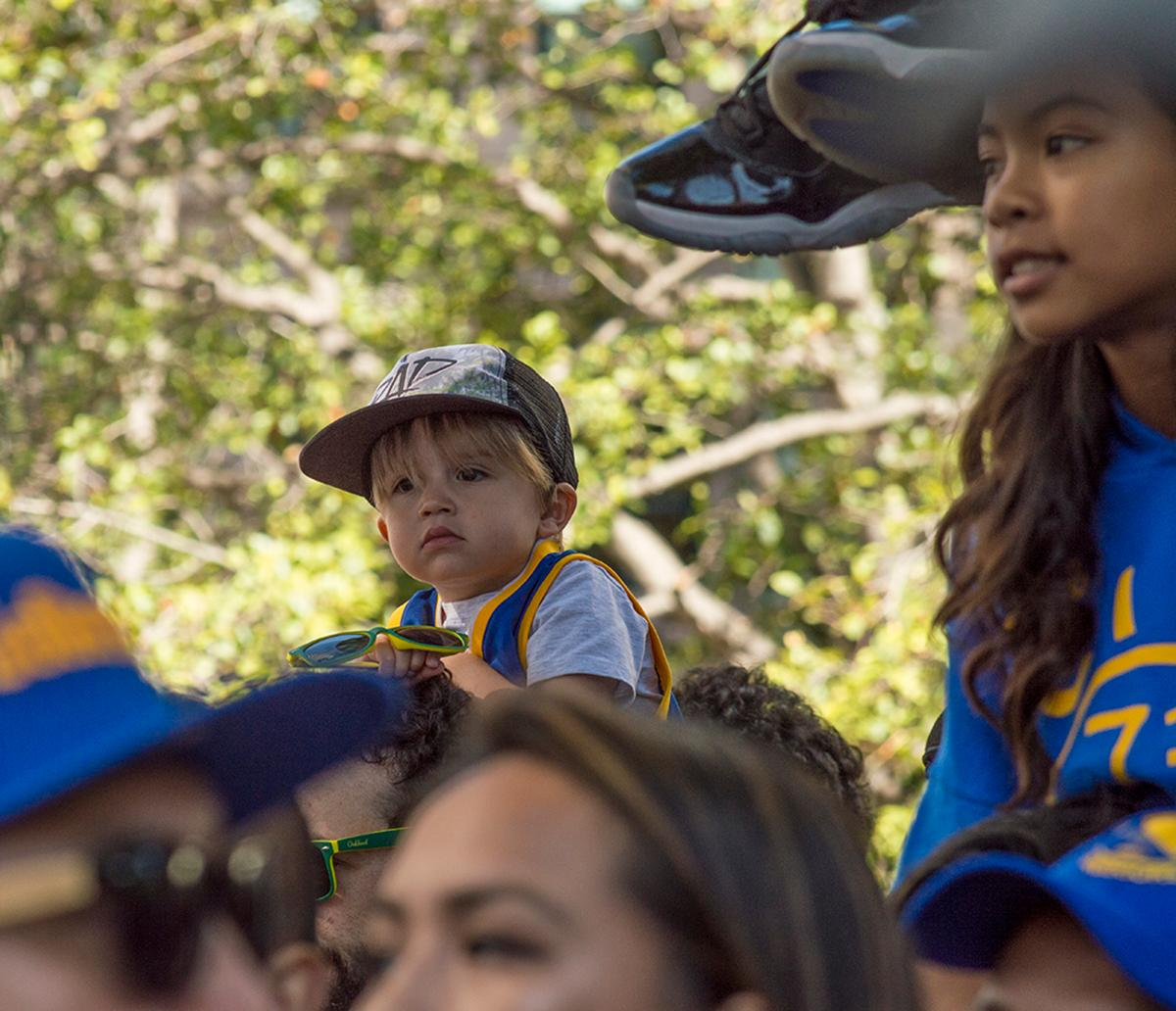 A young fan gets a great view of the Golden State Warriors victory parade in Oakland, California. Fans on 13th Street in Oakland, California. Photo by Emily Gonzalez, Oregon News Lab.