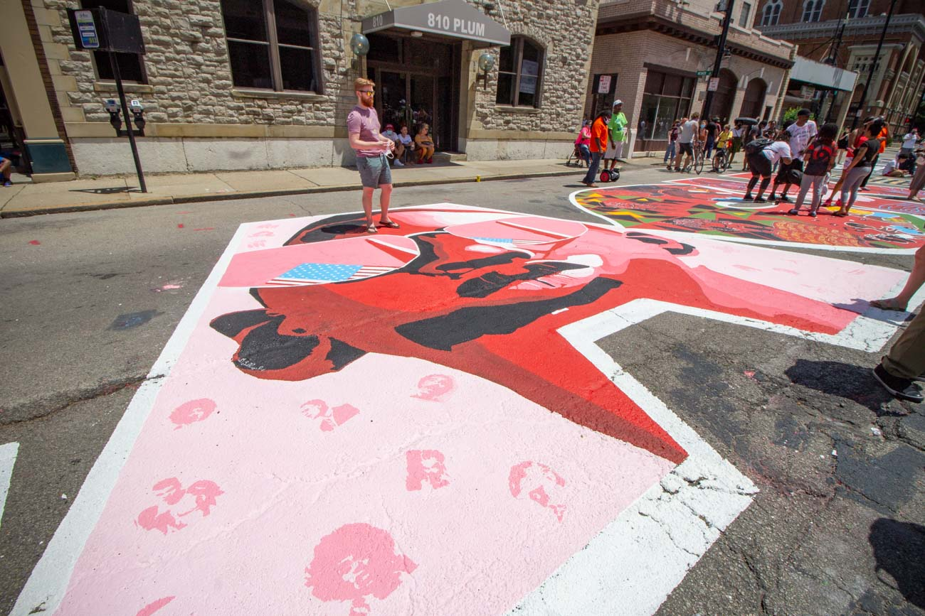 Cincinnati's newest mural isn't on the side of a building; it's on a very important street! Organizers and artists came together during the week to create an enormous Black Lives Matter mural on Plum Street between 8th and 9th Streets. The finished project will reflect the work of 17 black, local artists. The exclamation mark at the end of the mural will feature the work of all 17 artists in one character to signify equality. It was unveiled on June 19th, otherwise known as Juneteenth—a holiday memorializing the final day of slavery in the United States. The project was approved by the mayor and city council. / Image: Katie Robinson, Cincinnati Refined // Published: 6.19.20