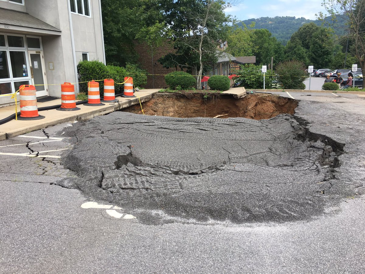 The sinkhole on Merrimon Avenue is getting larger. (Photo credit: WLOS staff)