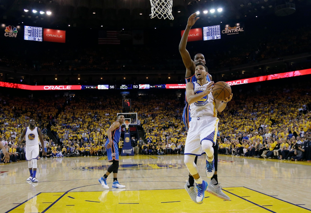 Golden State Warriors' Stephen Curry, right, drives past Oklahoma City Thunder's Kevin Durant, behind Curry, during the first half in Game 5 of the NBA basketball Western Conference finals Thursday, May 26, 2016, in Oakland, Calif. (AP Photo/Marcio Jose Sanchez)