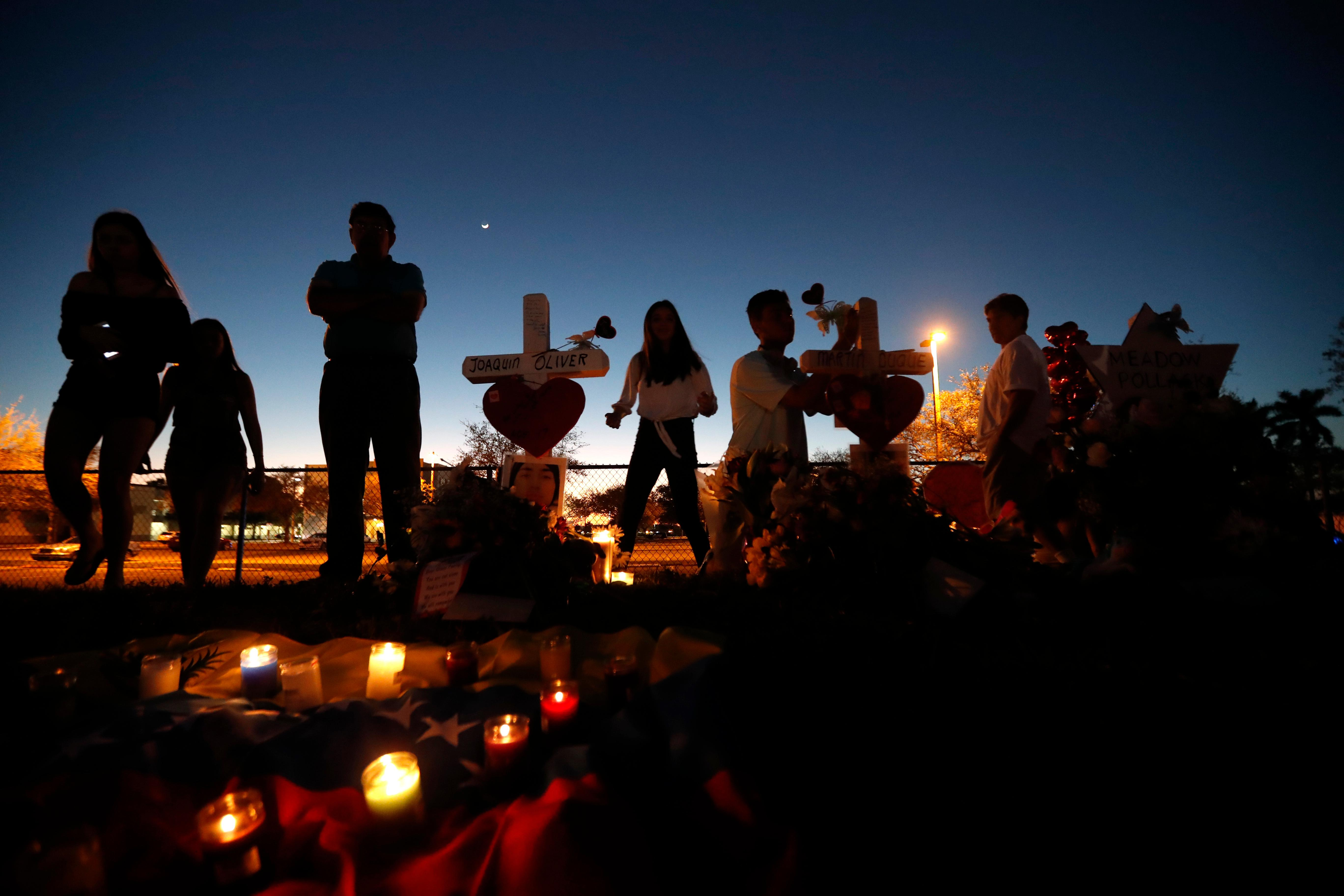 People visit a makeshift memorial outside Marjory Stoneman Douglas High School, where 17 students and faculty were killed in Wednesday's mass shooting in Parkland, Fla., Sunday, Feb. 18, 2018. Nikolas Cruz, a former student, was charged with 17 counts of premeditated murder on Thursday. (AP Photo/Gerald Herbert)