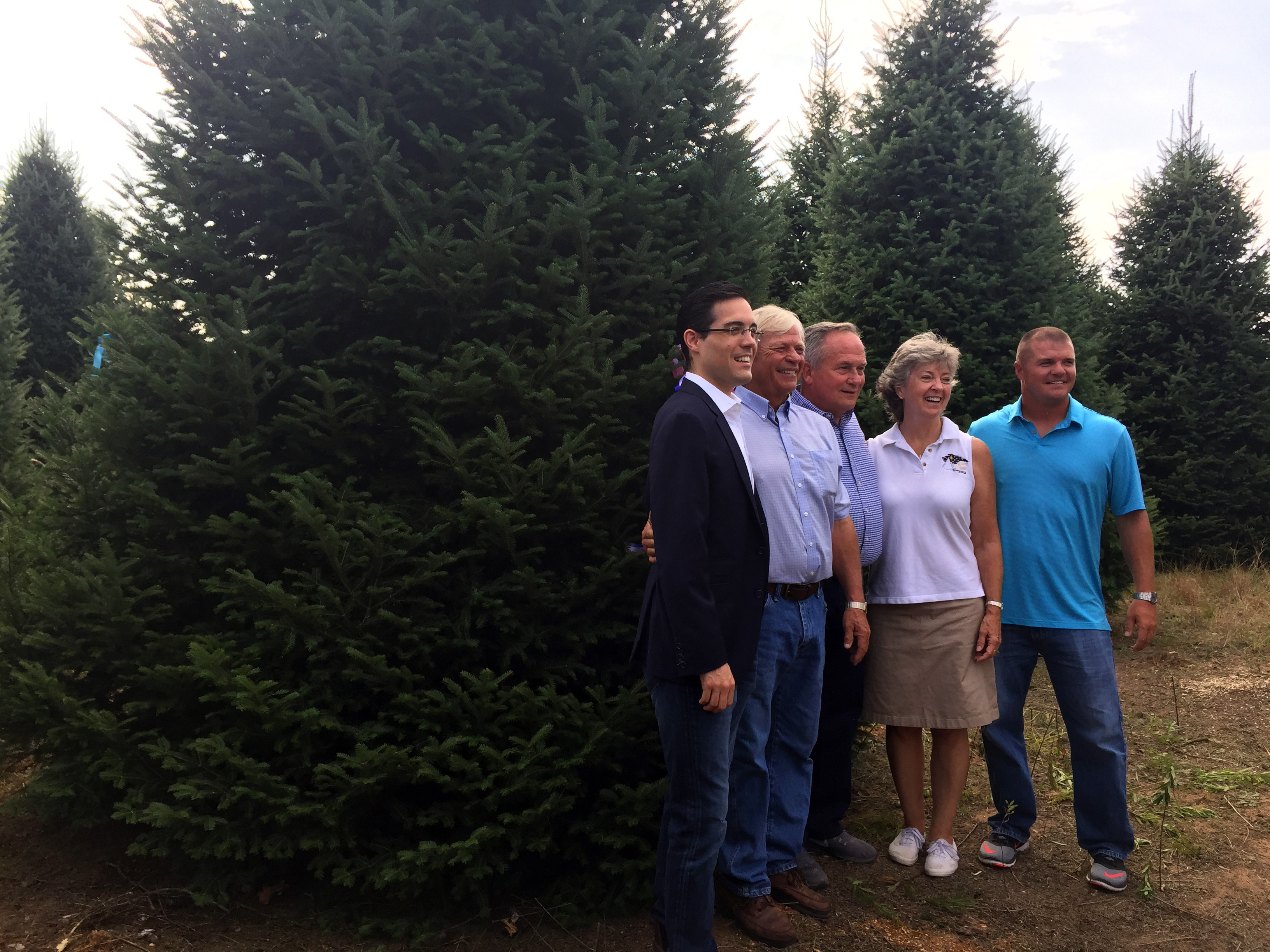 L-R: Timothy Harleth,  chief usher at the White House; Dale Haney, White House grounds superintendent; and Jim, Diane and David Chapman of Silent Night Evergreens pose for a photo Sept. 25, 2017, at Hanauer's Tree Farms in Shawano County. The tree behind them was selected as the official Christmas tree for the Blue Room in the White House. (WLUK/Pafoua Yang)