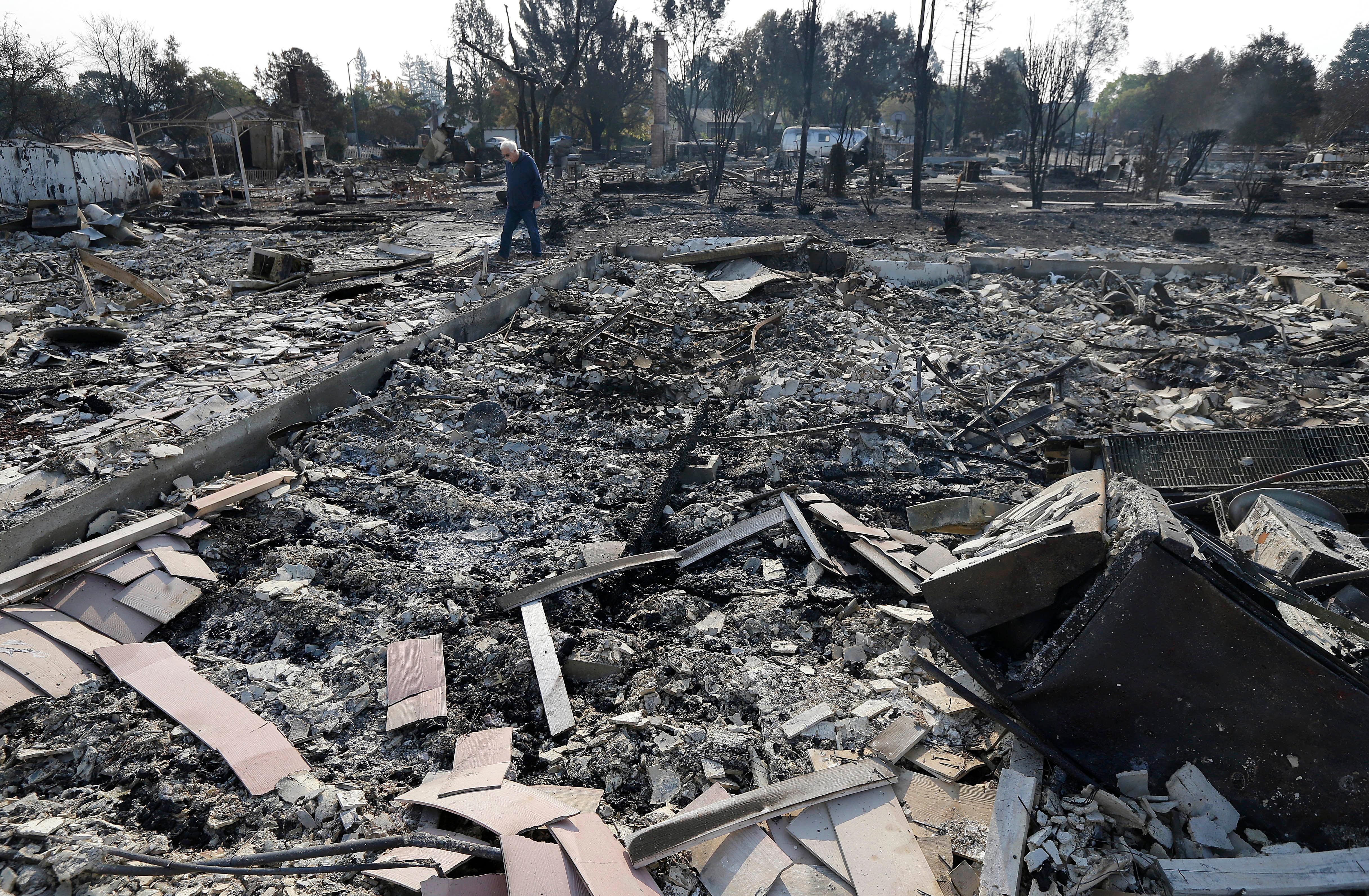 Phil Rush walks through the burnt remains at the site of his home destroyed by fires in Santa Rosa, Calif., Wednesday, Oct. 11, 2017. Wildfires tearing through California's wine country continued to expand Wednesday, destroying hundreds more homes and structures and prompting new evacuation orders. (AP Photo/Jeff Chiu)