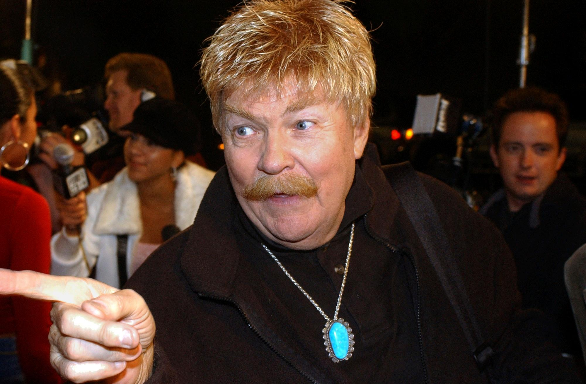 FILE - In this Monday, Oct. 21, 2002, file photo, comedian Rip Taylor talks with reporters before a film premiere, in the Hollywood section of Los Angeles. Taylor, the mustached comedian with a fondness for confetti-throwing who became a television game show mainstay in the 1970s, died Sunday, Oct. 6, 2019. He was 84. (AP Photo/Rene Macura, File)