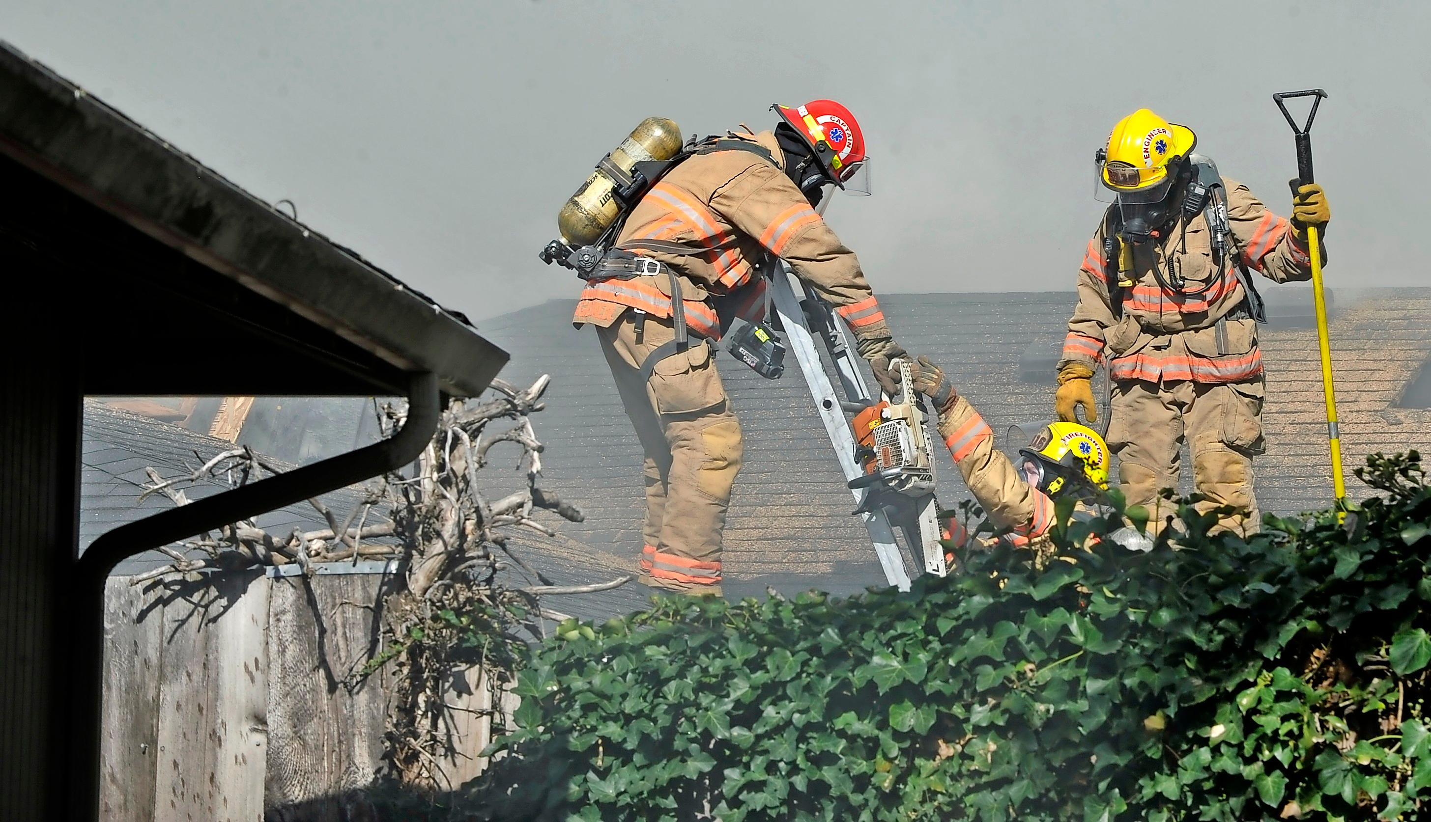 Firefighters work on the roof of a fully involved house fire near Bowmont Circle and Siskiyou Boulevard in Medford.