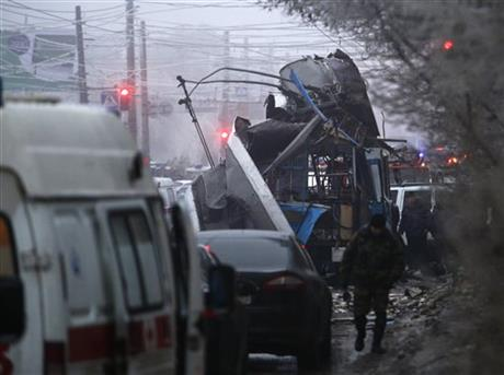 Experts and police officers examine a site of a trolleybus explosion, background, in Volgograd, Russia Monday, Dec. 30, 2013. The explosion on the trolleybus left at least 10 people dead Monday, a day after a suicide bombing  killed at least 17.