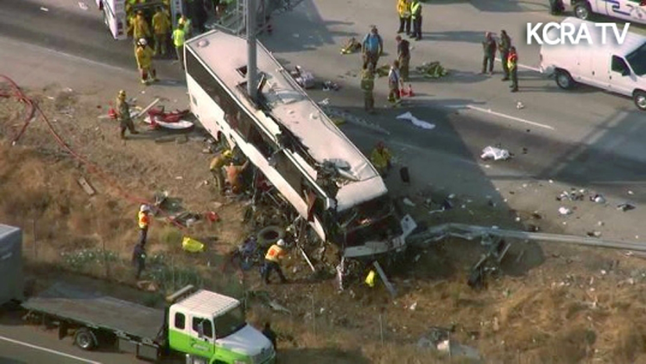 This still frame from video provided by KCRA3-TV shows authorities investigating the scene of a charter bus crash on northbound Highway 99 between Atwater and Livingston, Calif., Tuesday, Aug. 2, 2016. The bus veered off the central California freeway before dawn Tuesday and struck a pole that sliced the vehicle nearly in half, authorities said. (KCRA3-TV via AP) MANDATORY CREDIT TV OUT