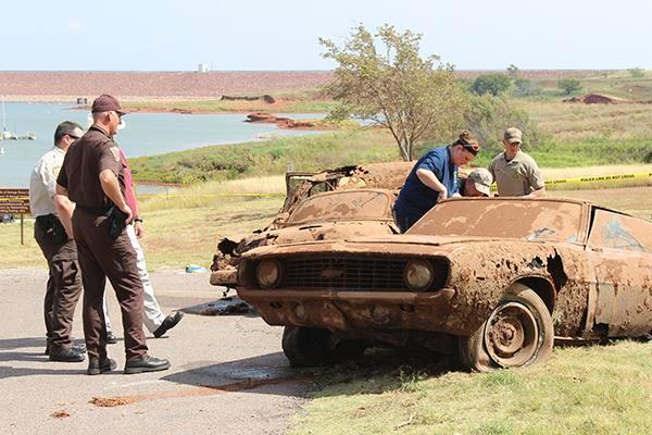 Authorities examine vehicles pulled out of Foss Lake.