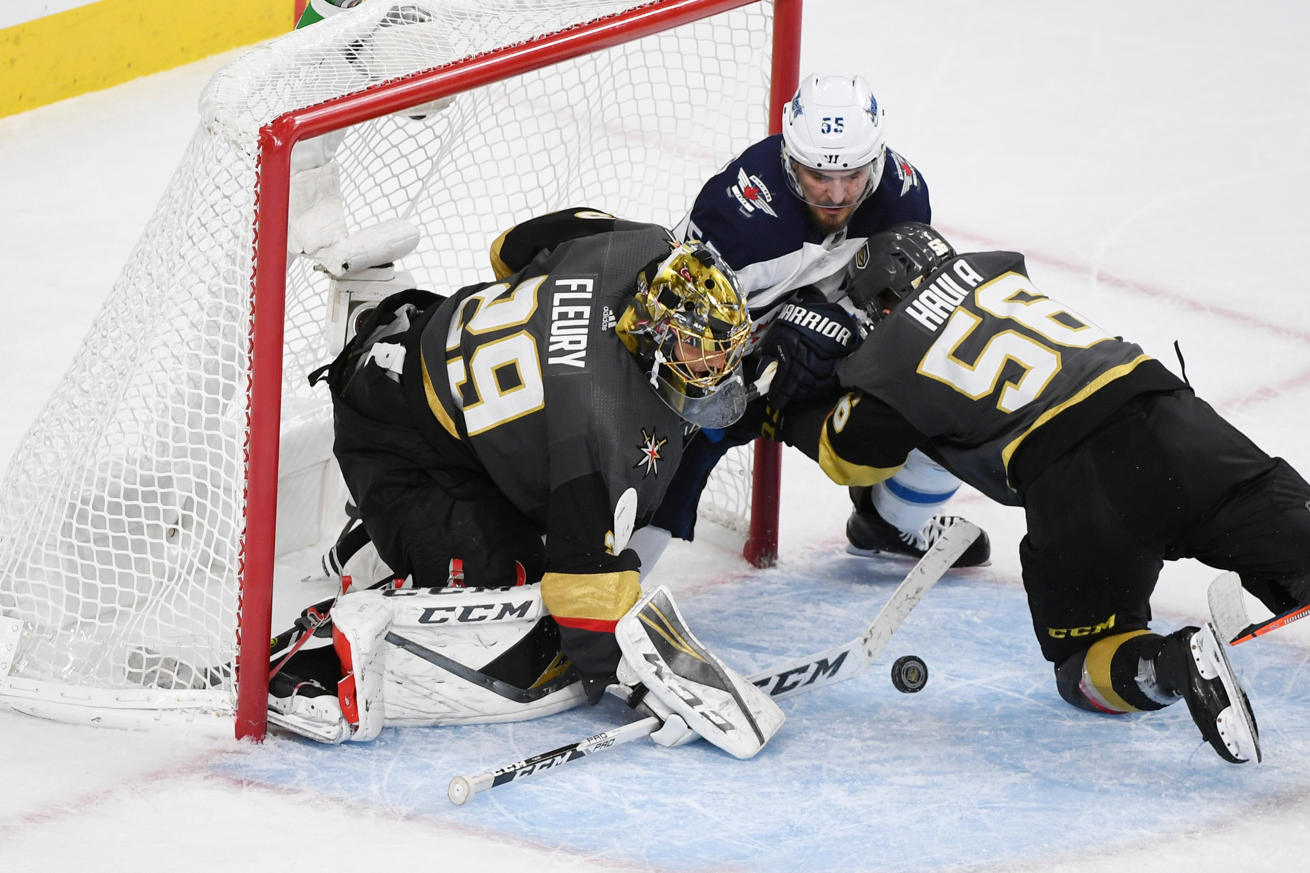 Vegas Golden Knights left wing Erik Haula (56) shoves Winnipeg Jets center Mark Scheifele (55) into the net as Vegas Golden Knights goaltender Marc-Andre Fleury (29) stops a shot during Game 3 of their NHL hockey Western Conference Final game Wednesday, May 16, 2018, at T-Mobile Arena. The Golden Knights won 4-2 to take a 2-1 lead in the series. CREDIT: Sam Morris/Las Vegas News Bureau