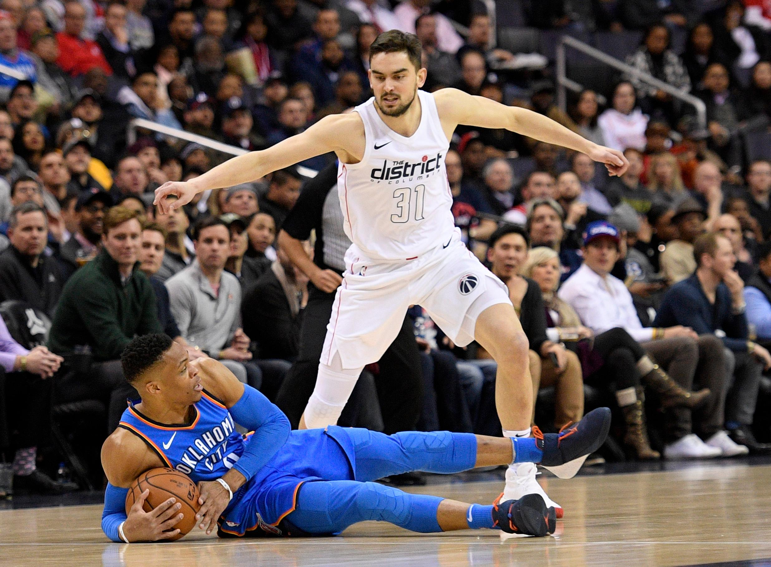 Oklahoma City Thunder guard Russell Westbrook, bottom, holds the ball against Washington Wizards forward Tomas Satoransky (31), of the Czech Republic, during the first half of an NBA basketball game, Tuesday, Jan. 30, 2018, in Washington. (AP Photo/Nick Wass)