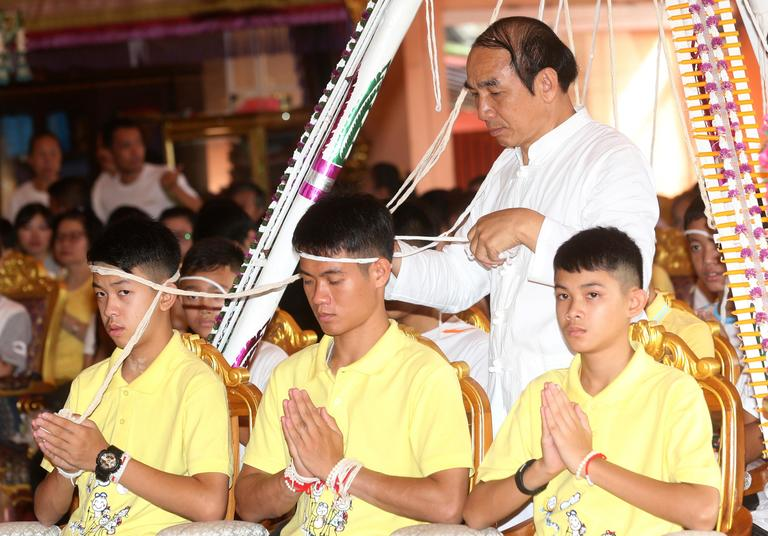 Soccer coach Ekkapol Janthawong, center, and members of the rescued soccer team attend a Buddhist ceremony that is believed to extend the lives of its attendees as well as ridding them of dangers and misfortunes in Mae Sai district, Chiang Rai province, northern Thailand, Thursday, July 19, 2018. The 12 boys and their soccer coach rescued from a cave in northern Thailand left the hospital where they had been recuperating and appeared at a news conference Wednesday, saying the ordeal made them stronger and taught them not to live carelessly. (AP Photo/Sakchai Lalit)