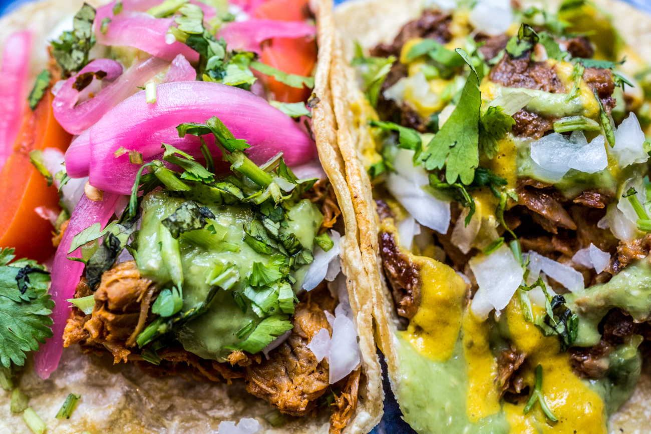 Conchinita (citrus-roasted pork) taco topped with avocado salsa and pickled chilis & a lengua (beef tongue) taco topped with avocado salsa and salsa amarilla / Image: Catherine Viox // Published: 8.31.19