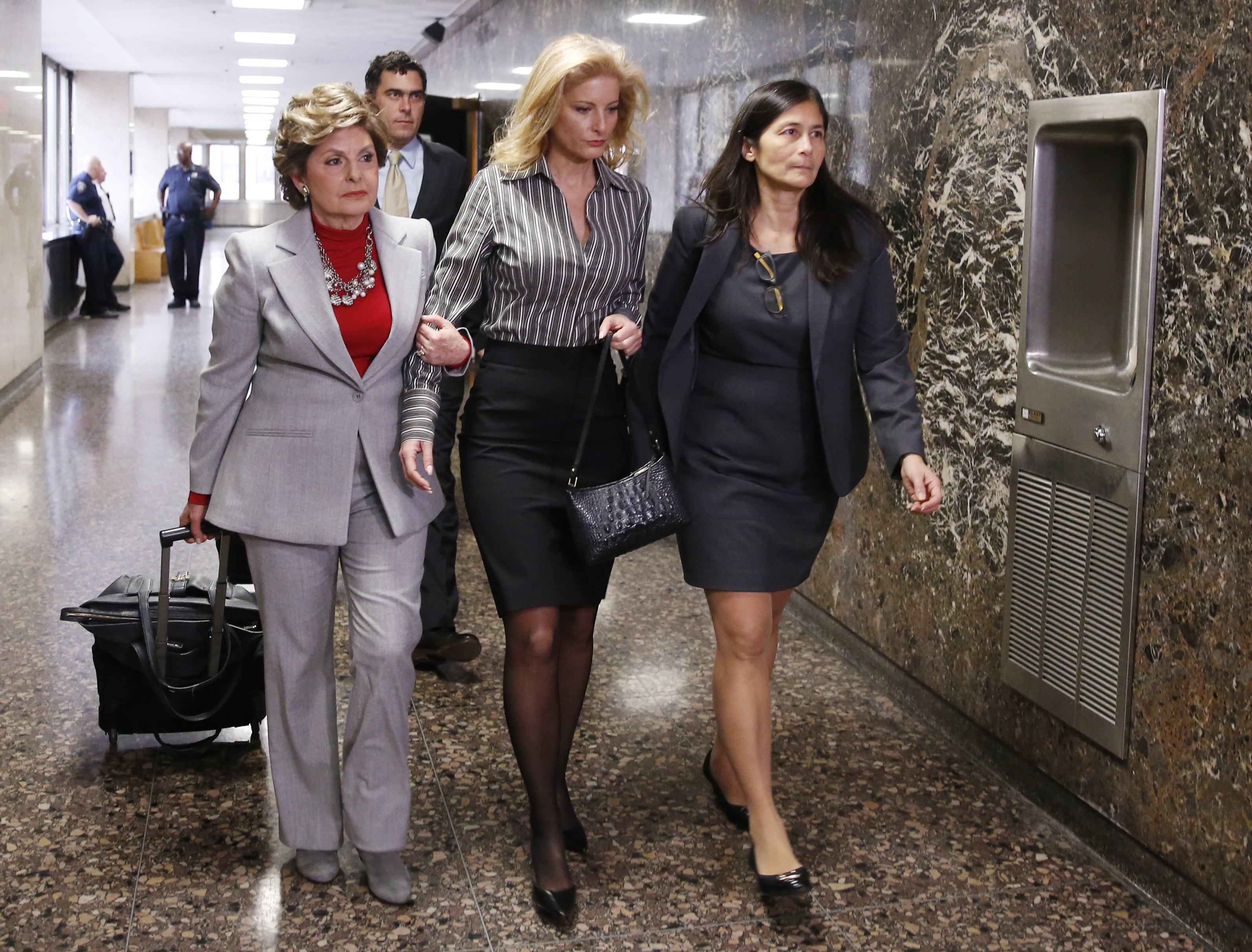 "Summer Zervos, center, a 2006 contestant on ""The Apprentice,"" enters Manhattan Supreme Court with attorney Gloria Allred, left, and an unidentified woman in New York, Tuesday, Dec. 5, 2017. A Manhattan judge is weighing whether to toss out a defamation lawsuit against President Donald Trump by the former contestant on his reality TV show ""The Apprentice"" who accused him of unwanted sexual contact. (AP Photo/Kathy Willens)"