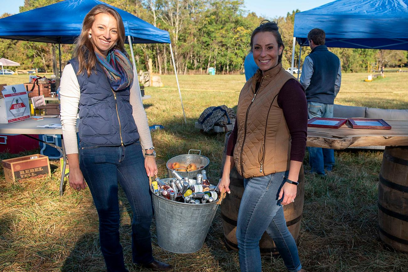 Dr. Allie Plettner and Julie Younts set up for their tailgate party with a tub of chilled champagne.{ }/ Image: Joe Simon // Published: 10.6.19