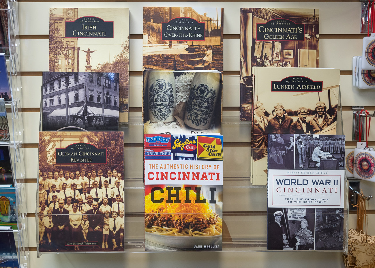 Local souvenirs, art, and books on Cincy history line the back wall of the shop. / Image: Phil Armstrong, Cincinnati Refined // Published: 12.13.18