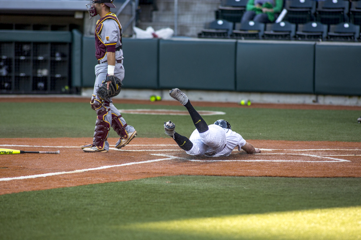 Ducks Ducks infielder Spencer Steer (#13) slides into home base with ease. The Oregon Ducks defeated the Arizona State Sun Devils 2-0 in the first game of a three game series Friday evening at PK Park in Eugene, Oregon. Photo by Duncan Moore, Oregon News Lab.