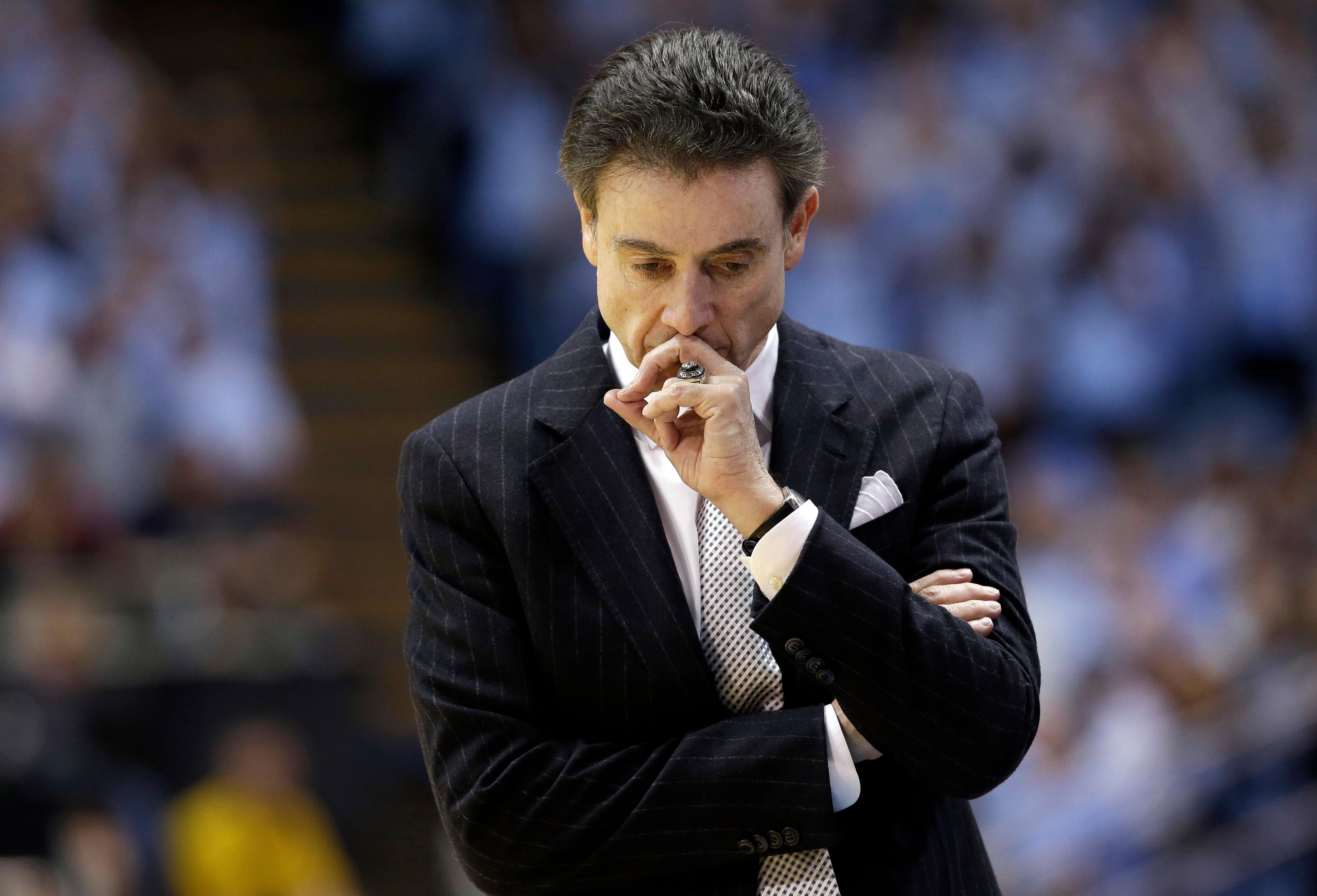FILE- In this Jan. 10, 2015, file photo, Louisville's coach Rick Pitino pauses during the first half of an NCAA college basketball game against North Carolina in Chapel Hill, N.C. The NCAA suspended Pitino, Thursday, June 15, 2017, for five ACC games following sex scandal investigation. A former men's basketball staffer is alleged to have hired strippers to entertain players and recruits.   (AP Photo/Gerry Broome, File)
