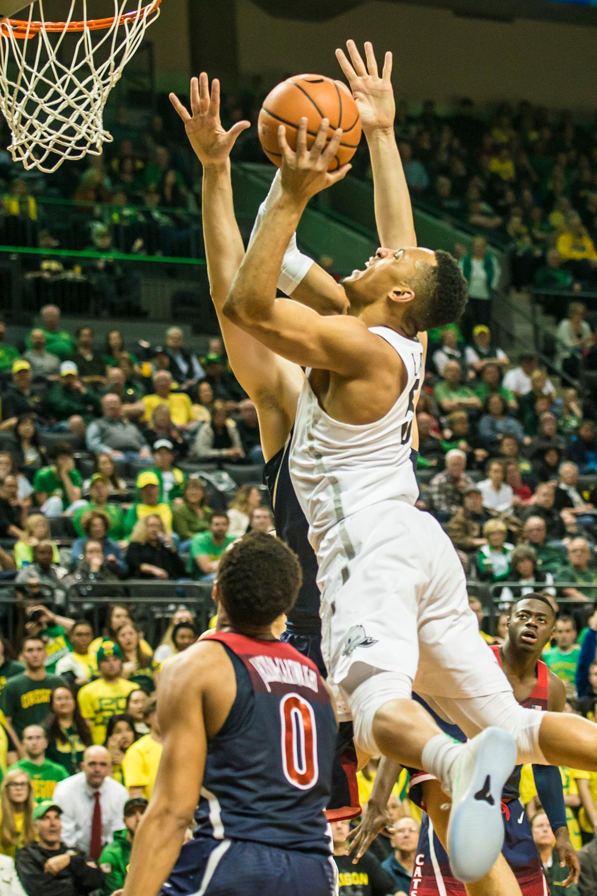 Oregon's Elijah Brown goes up for a layup against Arizona defenders in their matchup at Matthew Knight Arena Saturday. The Ducks upset the fourteenth ranked Wildcats 98-93 in a stunning overtime win in front of a packed house of over 12,000 fans for their final home game to improve to a 19-10 (9-7 PAC-12) record on the season. Oregon will finish out regular season play on the road in Washington next week against Washington State on Thursday, then Washington on the following Saturday. (Photo by Colin Houck)