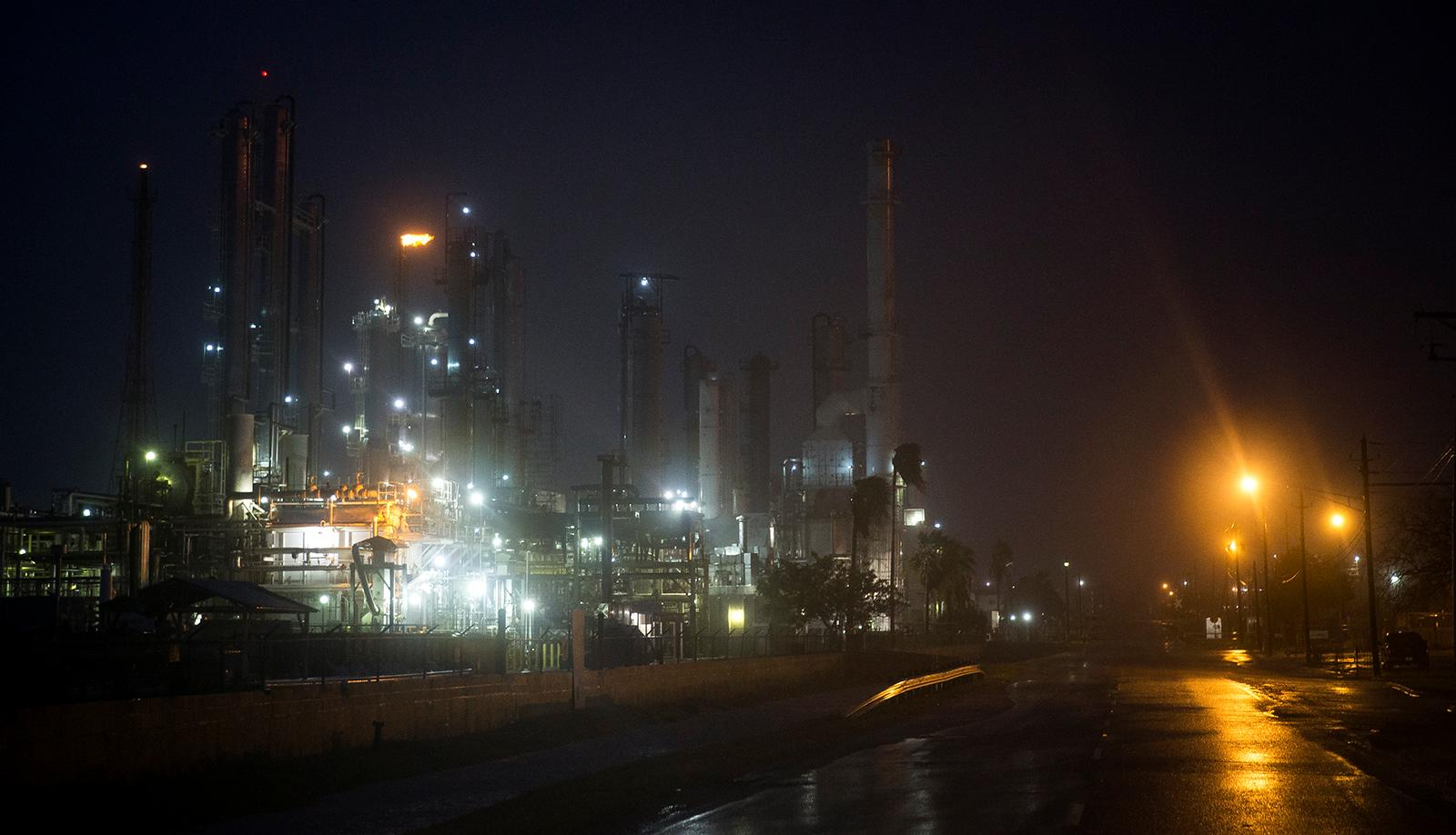 A Valero oil refinery's flare continues to burn as Hurricane Harvey makes landfall in Corpus Christi, Texas, on Friday, Aug. 25, 2017. Hurricane Harvey smashed into Texas late Friday, lashing a wide swath of the Gulf Coast with strong winds and torrential rain from the fiercest hurricane to hit the U.S. in more than a decade. (Nick Wagner/Austin American-Statesman via AP)