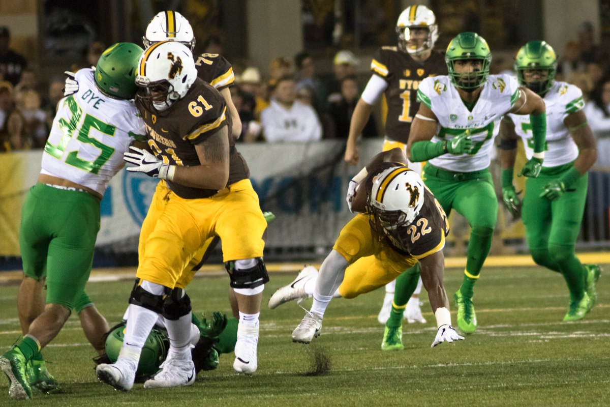 Wyoming running back Nico Evans (#22) shakes off an Oregon tackler. The Oregon Ducks recorded their first road win under head coach Willie Taggart with their 49-13 victory over the Wyoming Cowboys on a cold night at War Memorial Stadium in Laramie, Wyoming.  Photo by Austin Hicks, Oregon News Lab
