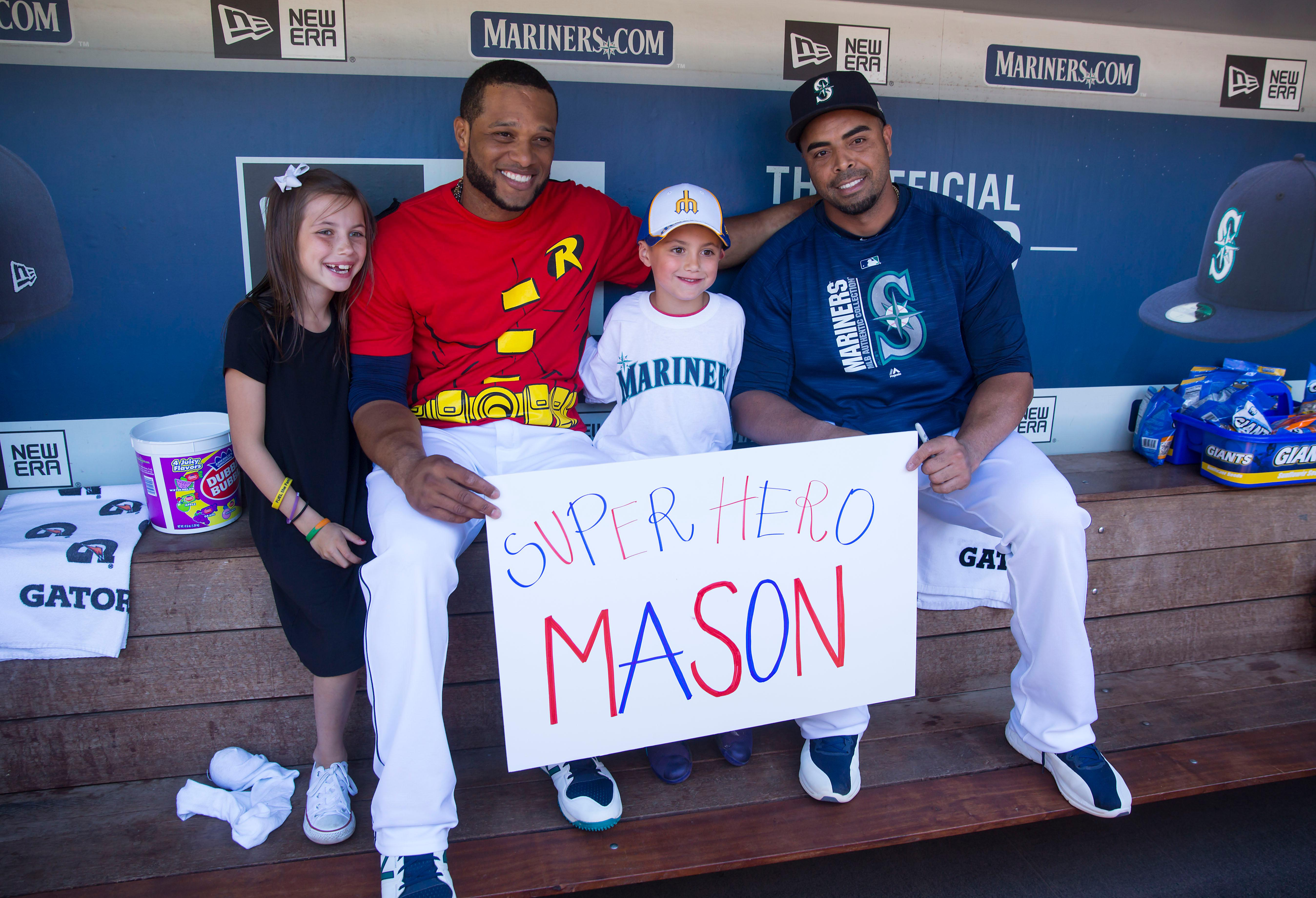 "Seven-year-old kidney cancer survivor Mason Nettleton, center, hangs out with Seattle Mariners Robinson Cano, left, and Nelson Cruise, right, as Nettleton served Seattle as a ""Superhero for a Day"" on Tuesday, June 27, 2017. (Sy Bean/ Seattle Refined)"