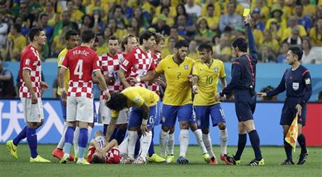 Referee Yuichi Nishimura from Japan gives Brazil's Neymar (10) a yellow card during the group A World Cup soccer match between Brazil and Croatia, the opening game of the tournament, in the Itaquerao Stadium in Sao Paulo, Brazil, Thursday, June 12, 2014.