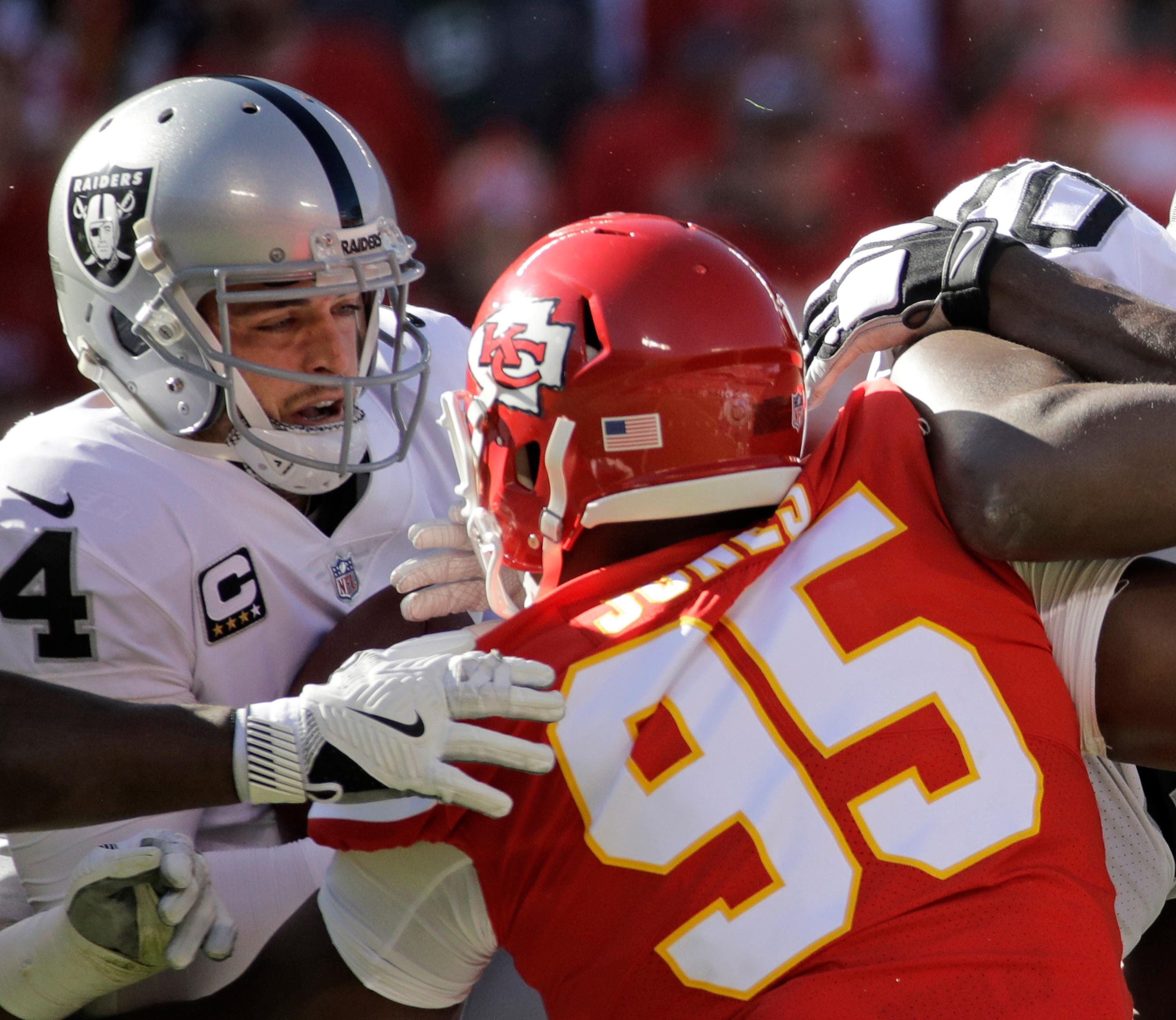 Kansas City Chiefs defensive lineman Chris Jones (95) sacks Oakland Raiders quarterback Derek Carr (4) during the first half of an NFL football game in Kansas City, Mo., Sunday, Dec. 10, 2017. (AP Photo/Charlie Riedel)