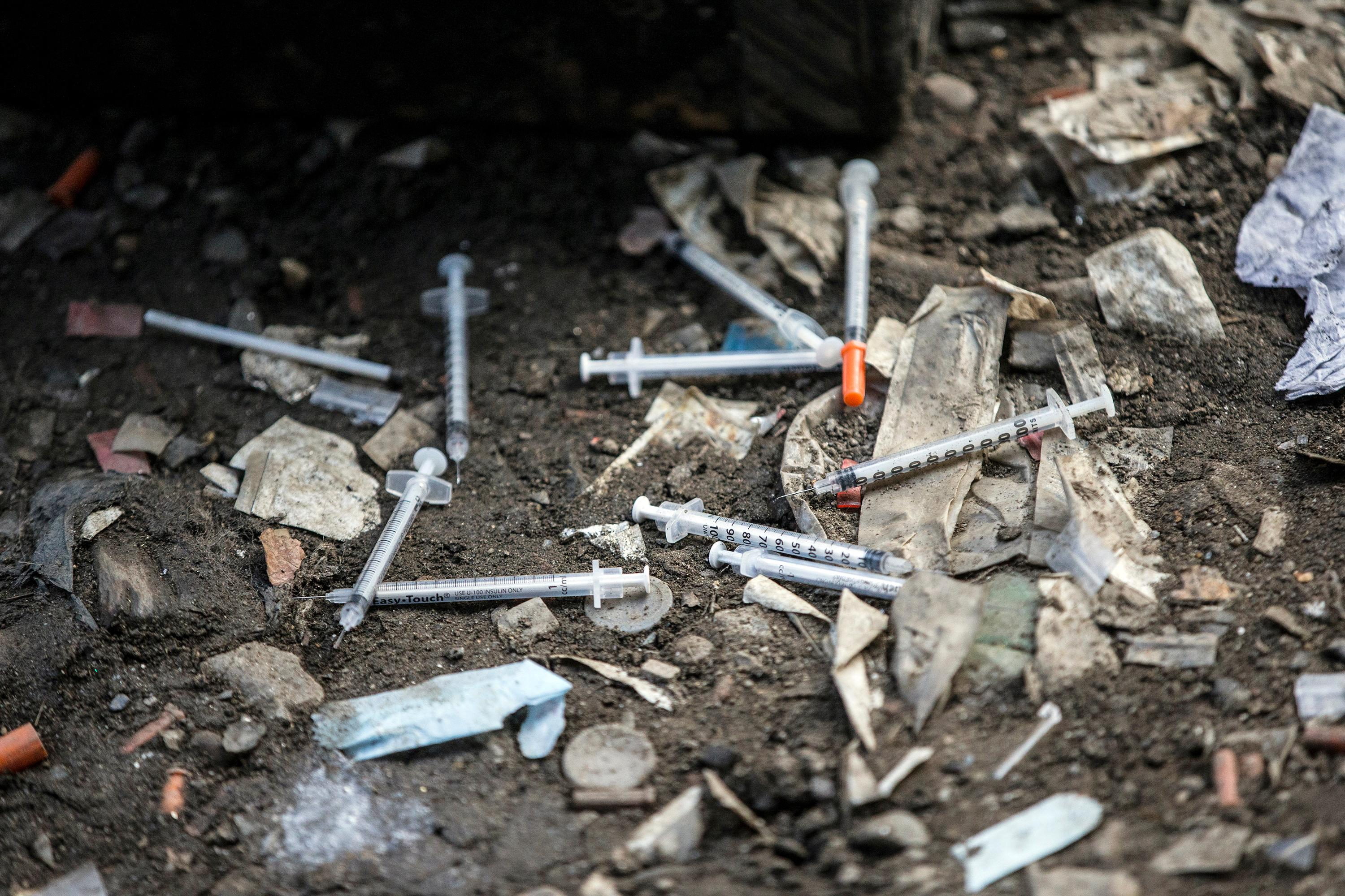 FILE – In this Feb. 2, 2017, file photo, used needles litter the ground at an open air drug market along Conrail train tracks in the Kensington section of Philadelphia. (Michael Bryant /The Philadelphia Inquirer via AP, File)<p></p>