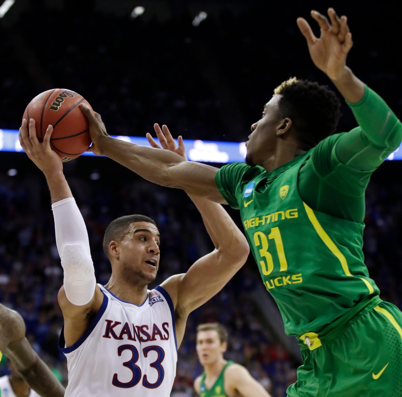 Kansas forward Landen Lucas (33) tries to pass over Oregon guard Dylan Ennis (31) during the first half of the Midwest Regional final of the NCAA men's college basketball tournament, Saturday, March 25, 2017, in Kansas City, Mo. (AP Photo/Charlie Riedel)
