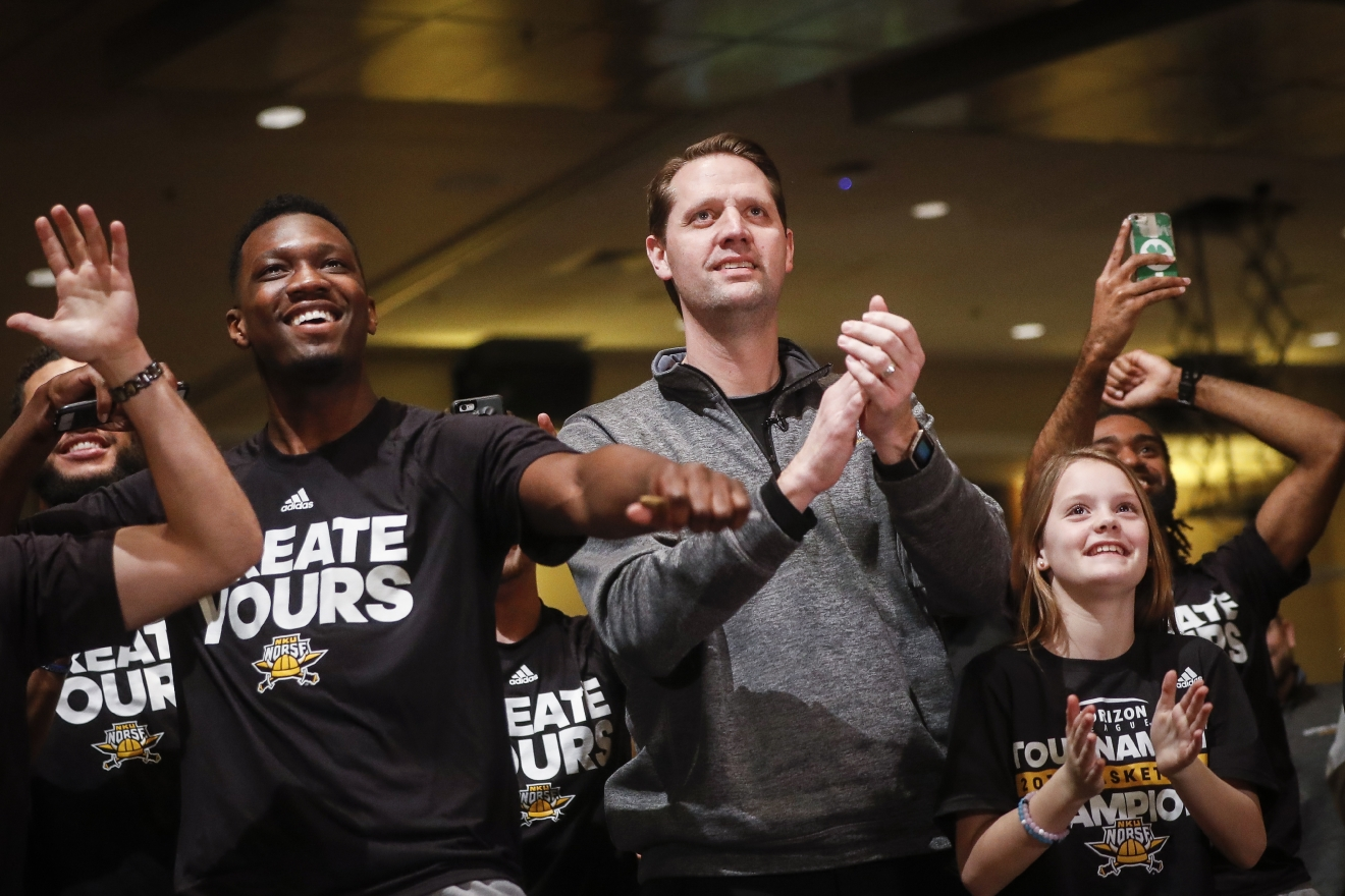 Northern Kentucky men's basketball coach John Brannen, center, celebrates after the team's matchup against Kentucky was announced for the NCAA men's basketball tournament, Sunday, March 12, 2017, in Highland Heights, Ky. NKU secured an automatic berth after winning the Horizon League championship to become the second team since 1970 to be selected for the tournament in its first eligible season. (AP Photo/John Minchillo)