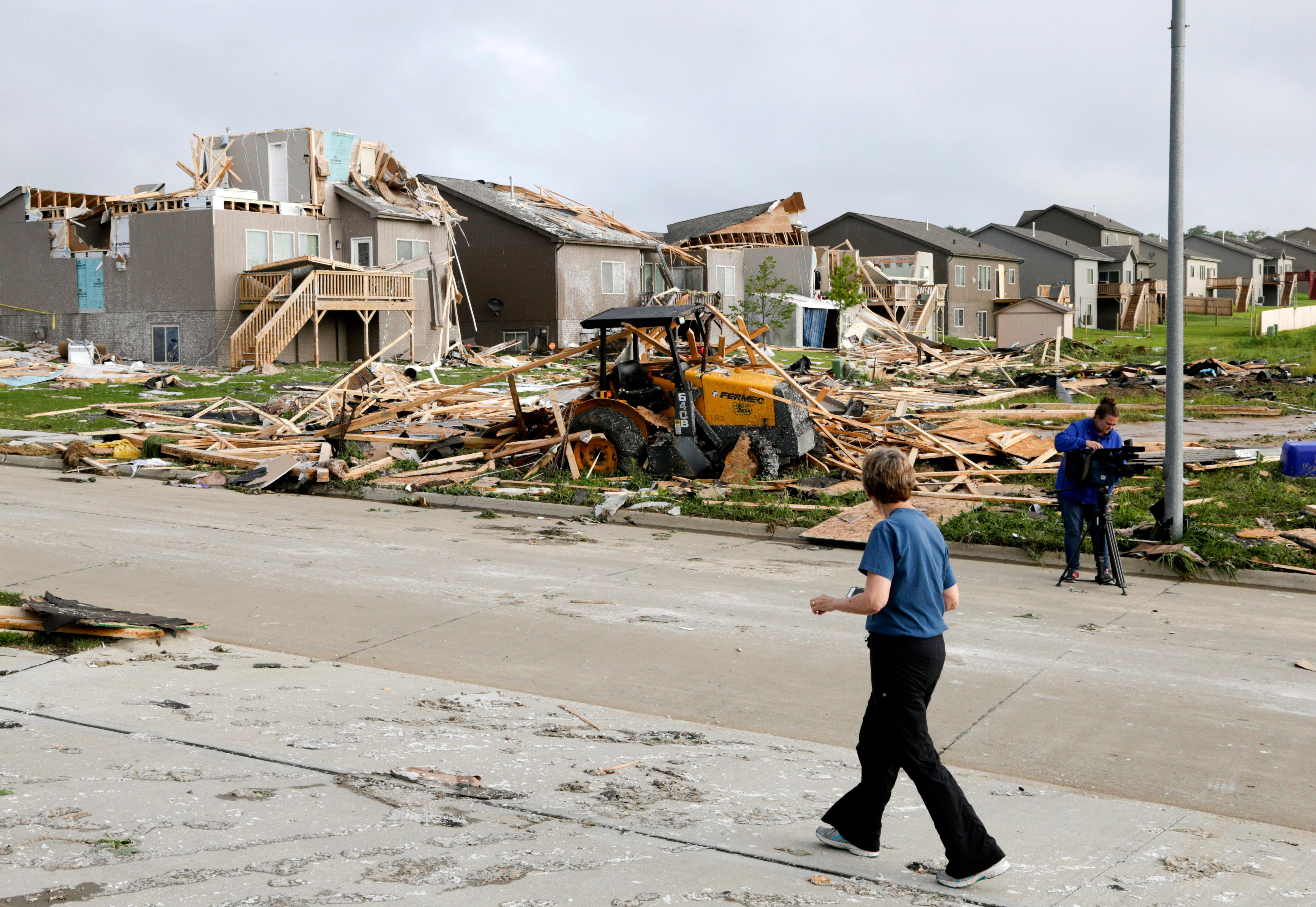 A neighbor walks past damaged homes in the Hyda Hills neighborhood in Bellevue, Neb., Saturday, June 17, 2017. A severe weather front passed through the area the previous evening. (AP Photo/Nati Harnik)