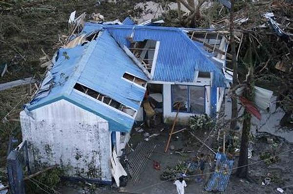 Residents sift through the rubble of their damaged house following a powerful typhoon that hit Tacloban city, in Leyte province, central Philippines Saturday, Nov. 9, 2013.
