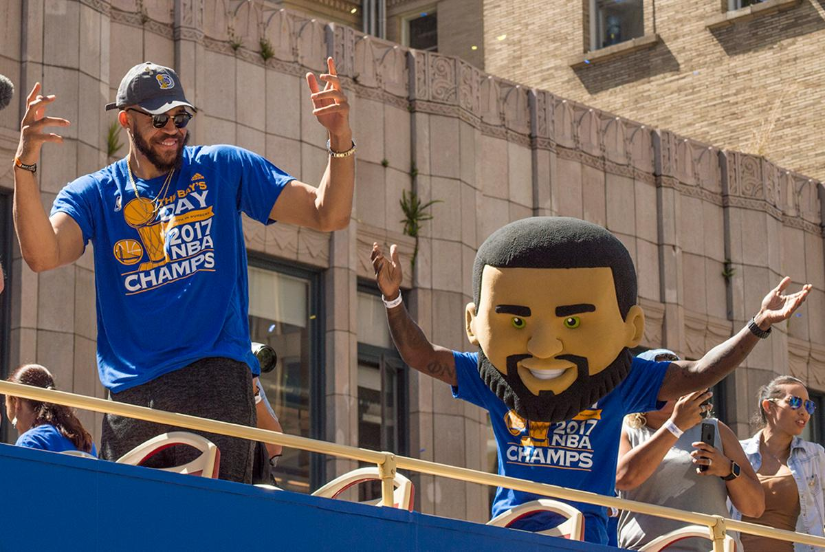 JaVale McGee and his twin greet fans atop his double decker bus in the Golden State Warriors victory parade in Oakland, California. Photo by Emily Gonzalez, Oregon News Lab.