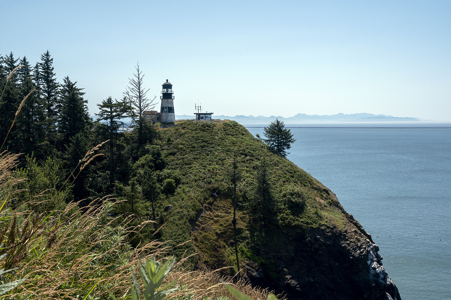 The oldest lighthouse in Washington, Cape Disappointment Lighthouse, opened in 1856, standing at 53 feet tall and used to provide navigational aid to marine traffic entering from the south. Uniquely, a 1,600-pound bronze bell once issued a fog warning but was discontinued shortly after due to the discovery of dead spots. Several renovations occurred over decades, including updated rotational lights in 1950, full automation in 1998 with lights shining 17 miles out to sea, and a new black and white stripe paint design. (Image: Rachael Jones / Seattle Refined)