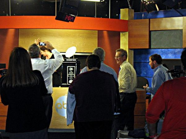 ABC 33/40 employees snap pictures of the BCS trophy.
