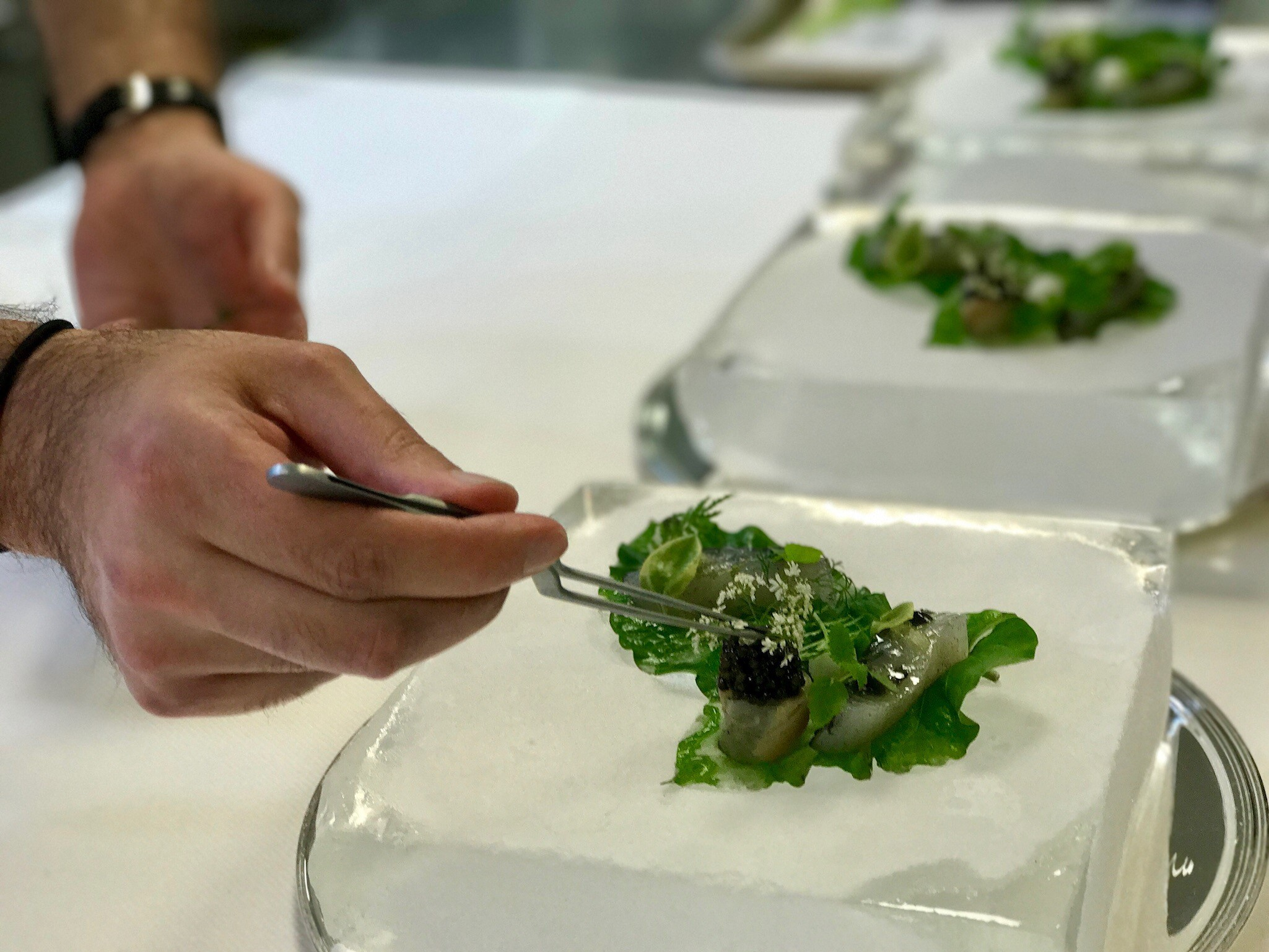 Chef Paul Liebrandt perfecting his Mosaic of Madai dish on a fresh ice block. (Image: Courtesy The Watergate Hotel)