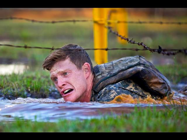 Army 2nd Lt. John Bergman low crawls through a water obstacle during the 31st annual Best Ranger Competition at Camp Rogers on Fort Benning, Ga., April 11, 2014. Bergman is assigned to the 25th Infantry Division.