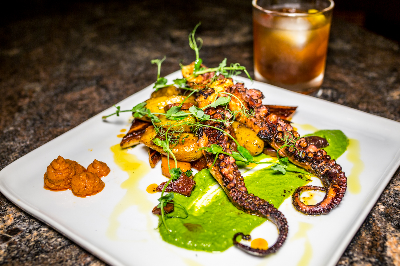 Octopus: fingerling potatoes, Spanish chorizo, charred carrots, romesco, and salsa verde  with The Woodhouse cocktail / Image: Catherine Viox // Published: 9.5.19
