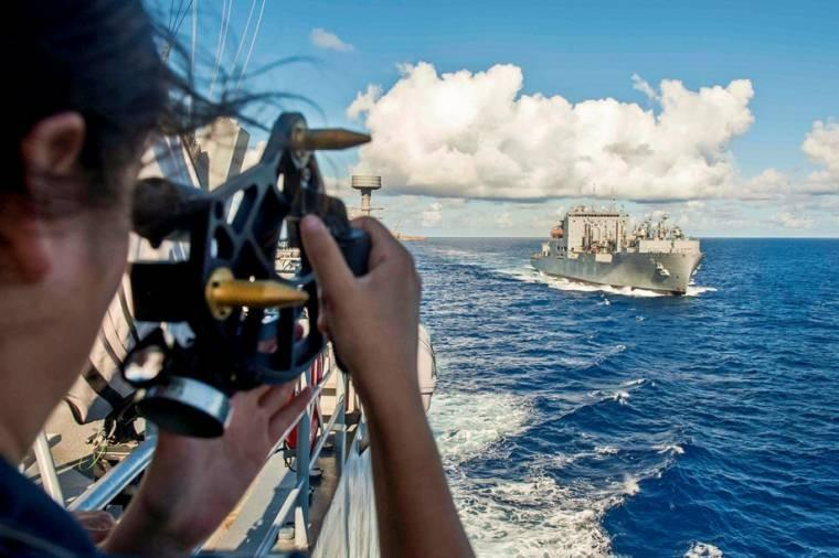 U.S. Navy Ensign Rachel Herrera uses a sextant to determine the distance from the amphibious dock landing ship USS Pearl Harbor to the Military Sealift Command dry cargo and ammunition ship USNS Mathew Perry before a replenishment at sea, Aug. 8, 2013.
