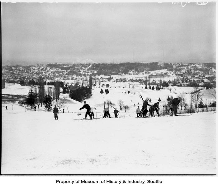 Record low temperatures and heavy snow plagued the Seattle area during the winter of 1950. On Friday January 13, downtown Seattle received an average of ten inches of snow, with Sea-Tac airport reporting 20 inches.  Although the snow let up on Saturday, the cold temperatures persisted for several more days. Seattle recorded nine days of temperatures below ten degrees between January 12 and February 4, 1950. In this photo, a group of skiers enjoy the hillside at the West Seattle golf course. (Photo: Museum of History & Industry, Seattle. Image: 1986.5.14567)