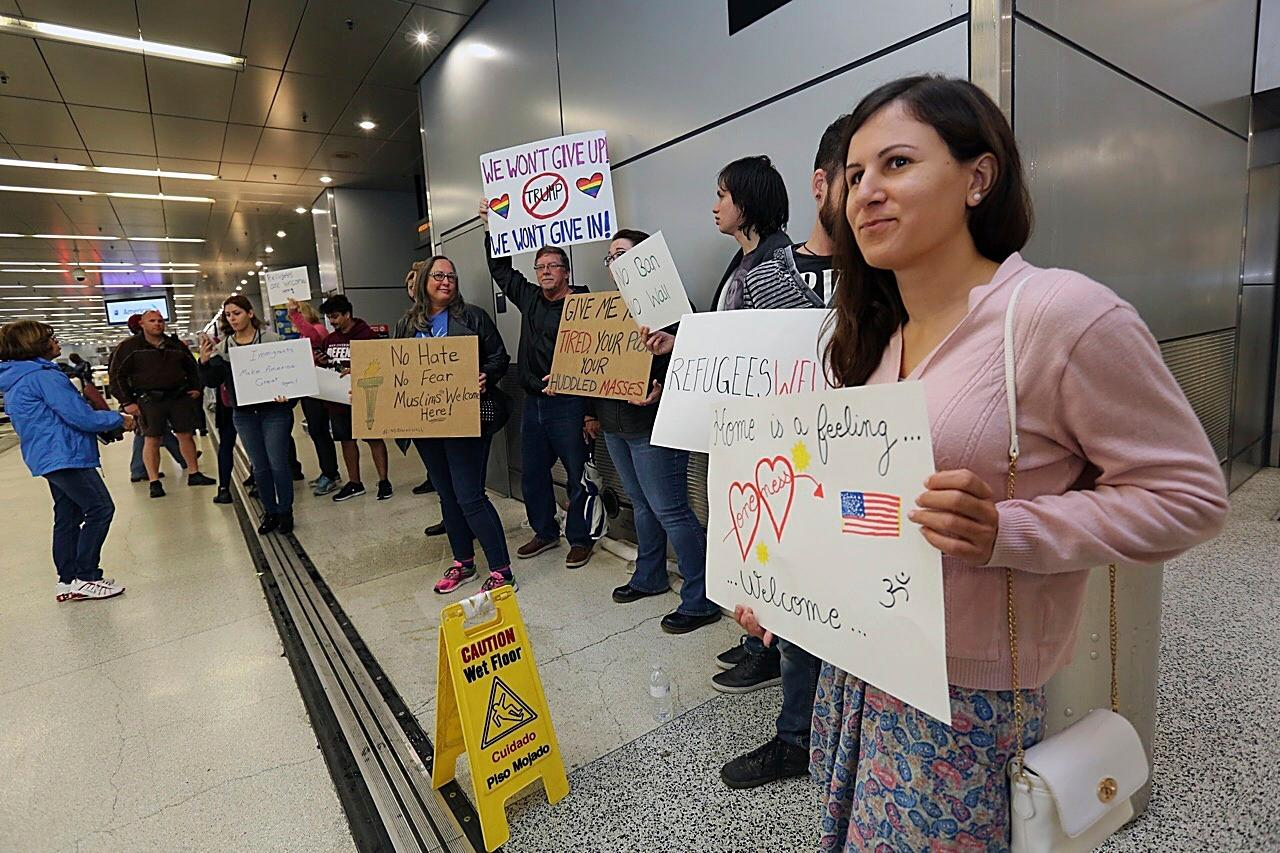 About 30 protesters demonstrate against President Trump's refugee ban at Miami International Airport on Sunday, Jan. 29, 2017. President Donald Trump's immigration order sowed more confusion and outrage across the country Sunday, with travelers detained at airports, panicked families searching for relatives and protesters registering their opposition to the sweeping measure. (C.M. Guerrero/El Nuevo Herald via AP)