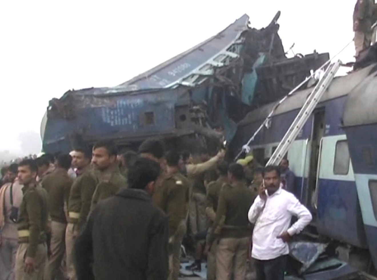 In this image made from video, India's security forces personnel gather at the site of a train accident near Pukhrayan, about 270 kilometers (168 miles) from Allahabad, Sunday, Nov. 20, 2016. Rescue workers used gas cutters to pull out survivors after 14 coaches of a passenger train rolled off the track in northern India early Sunday, police said. (KK Productions via AP)