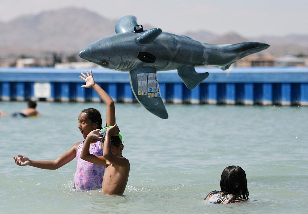 Carolina Colon tosses a shark water toy airborne while cooling off at Spring Valley Lake in Victorville Calif., Monday June 19, 2017. Airlines canceled flights in Phoenix and doctors urged people to be careful around concrete, playground equipment and vehicle interiors Monday as a punishing heat wave threatens to bring temperatures approaching 120 degrees to parts of the Southwestern U.S. (James Quigg/The Daily Press via AP)