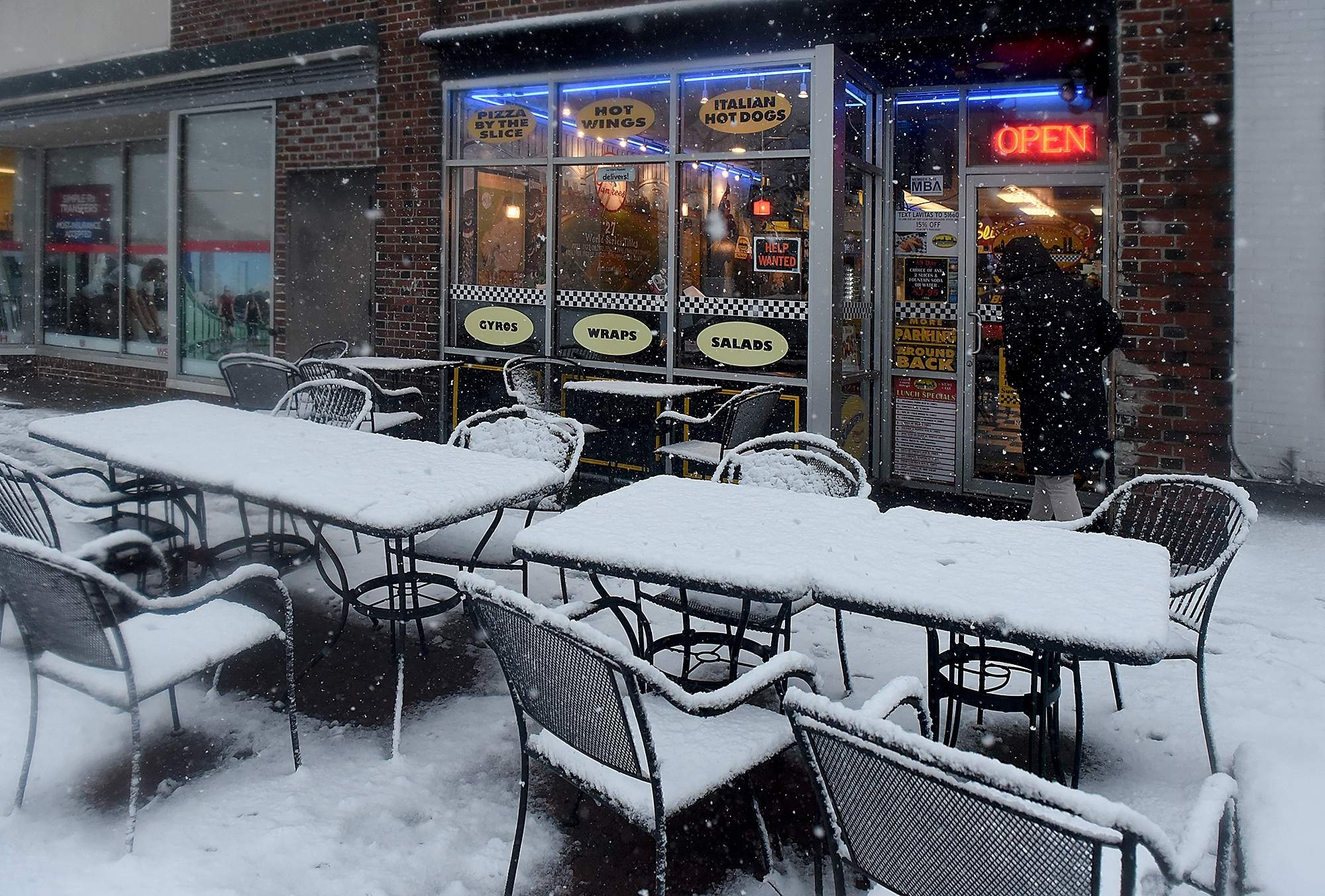 Erin Kyler, of Moorestown, heads into Lavita???s Pizzeria in moorestown, to pick up dinner for her family as the heavy snow comes down, Wednesday, March 7, 2018. [NANCY ROKOS / STAFF PHOTOJOURNALIST]