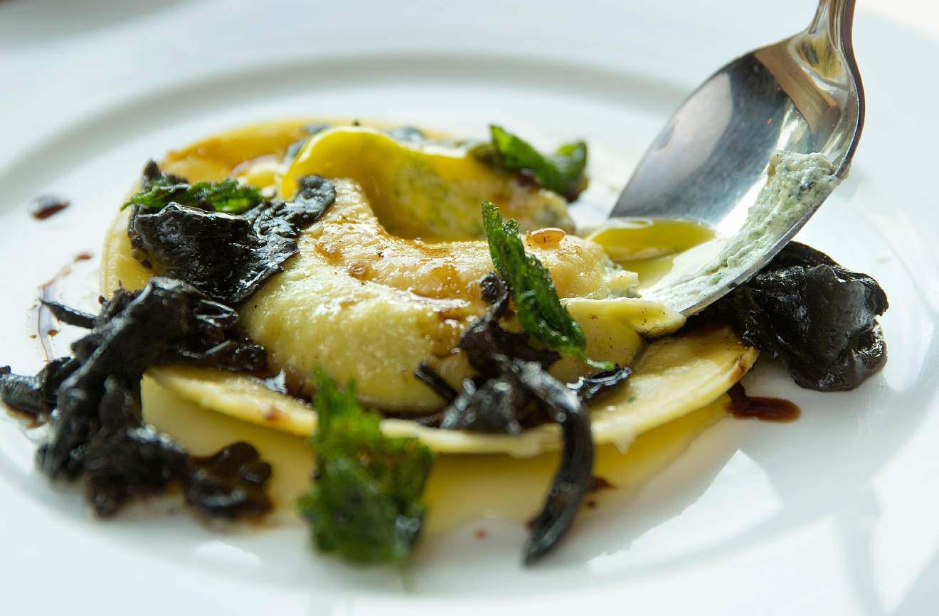 Chef Addam Buzzalini whips up a raviolo, with a duck egg, nettles, black trumpet, and brown butter, at Tavoláta Capitol Hill. (Sy Bean / Seattle Refined)