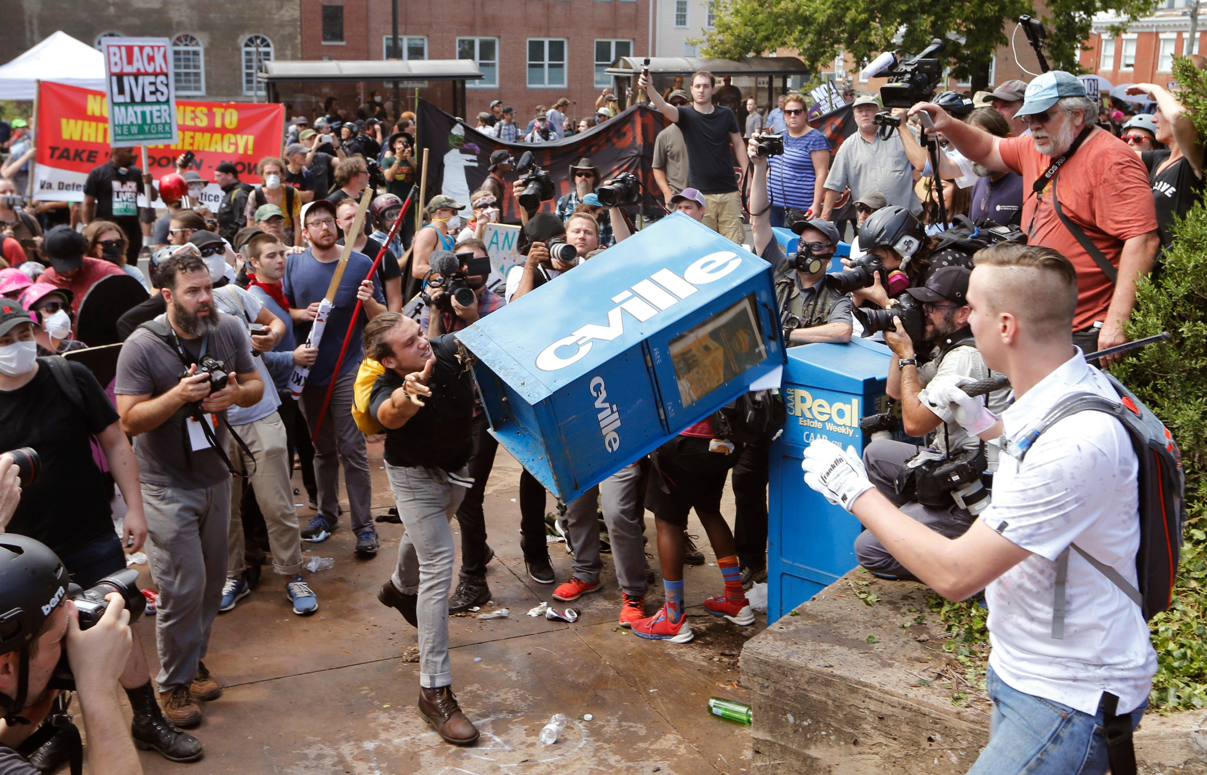 White nationalist demonstrators clash with a counter demonstrator  as he throws a newspaper box at the entrance to Lee Park in Charlottesville, Va., Saturday, Aug. 12, 2017. Gov. Terry McAuliffe declared a state of emergency and police dressed in riot gear ordered people to disperse after chaotic violent clashes between white nationalists and counter protestors. (AP Photo/Steve Helber) (AP Photo/Steve Helber)