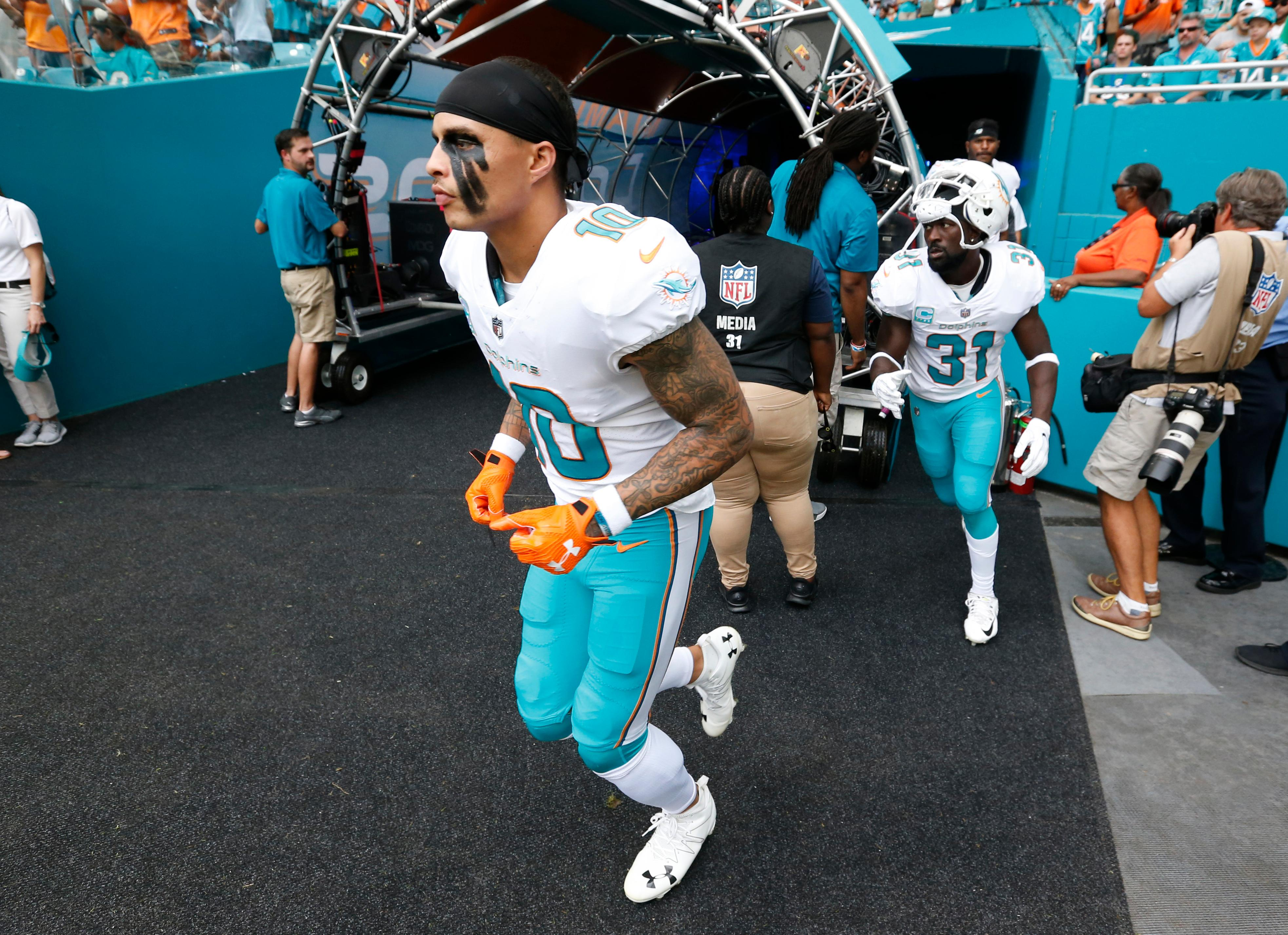 Miami Dolphins wide receiver Kenny Stills (10), free safety Michael Thomas (31) and Miami Dolphins tight end Julius Thomas (89), far right, enter the field after the National Anthem is played, during the first half of an NFL football game against the New York Jets, Sunday, Oct. 22, 2017, in Miami Gardens, Fla. (AP Photo/Wilfredo Lee)