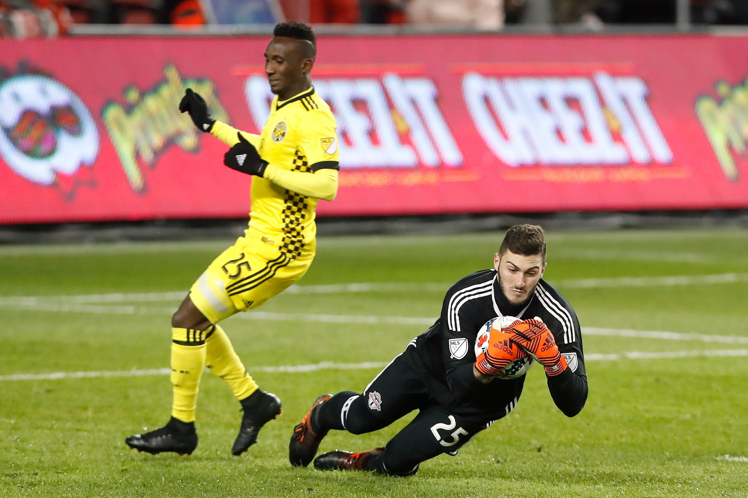 Toronto FC goalkeeper Alex Bono (25) makes a save in front of Columbus Crew defender Harrison Afful (25) during the second half of an Eastern Conference MLS final playoff soccer game, Wednesday, Nov. 29, 2017 in Toronto. (Mark Blinch/The Canadian Press via AP)