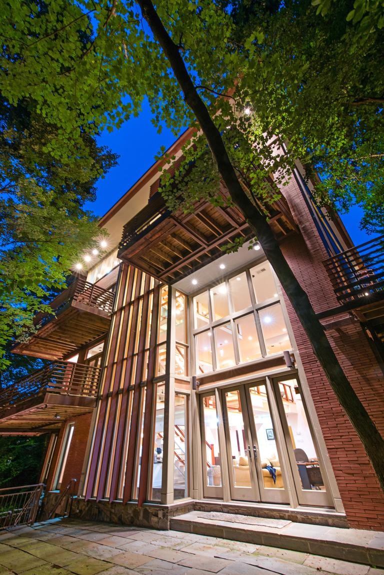 This incomparable masterpiece designed by Travis Price, FAIA., the doyen of contemporary architecture, was built with stunning red brick, warm wood, and exciting installations of glass which organically bring the exposures of Rock Creek Park into every level of the home. From the private cul de sac to the formal entry and dramatic great room, this home is impressive, surprising, and remarkably comfortable. The experience is maximized by the four stories of windows, interrupted only by cantilevered balconies that beg you to step outside among the treetops. There were no details missed, nothing spared, this is an elegant modern home in the gorgeous neighborhood of Forest Hills. (Image: Tony Brown)