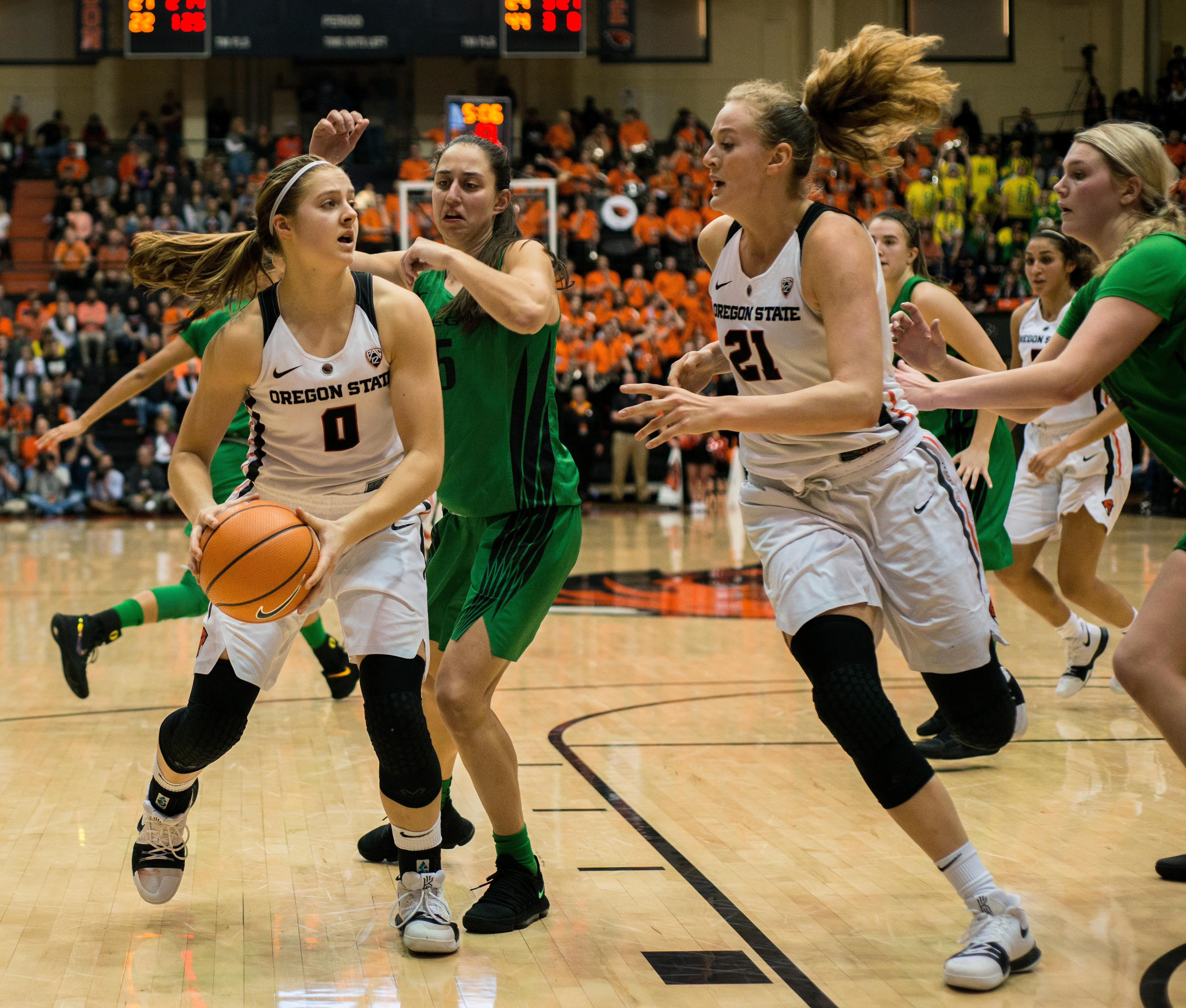 Oregon State Beavers guard Mikayla Pivec (#0) pushes past Oregon Ducks defense as Beavers forward Marie Gülich (#21) swoops in to take the pass.The Oregon Ducks were defeated by the Oregon State Beavers 85-79 on Friday night in Corvallis. Sabrina Ionescu scored 35 points and Ruthy Hebard added 24. The Ducks will face the Beavers this Sunday at 5 p.m. at Matthew Knight Arena. Photo by Abigail Winn, Oregon News Lab